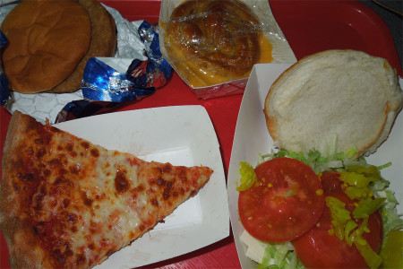 The four main vegetarian lunch choices, a veggie burger, cheese pretzel, cheese pizza, and a sandwich with four peices of cheese, in the cafeteria during first lunch May first.
