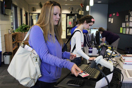 Using her 2013-2014 student ID, Hannah Busch (12), signs into the library, Sept. 22.