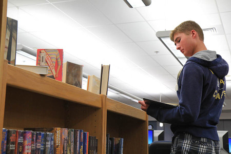 Searching for a book of choice, Ryan Atwood (11) scours the library, Sept. 9.