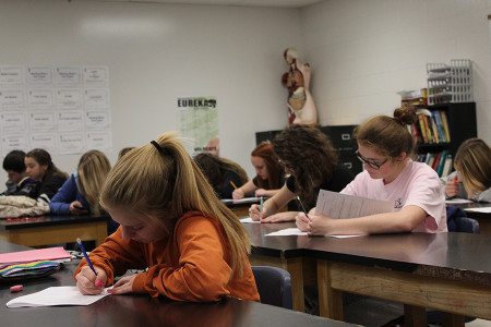 Megan Hammel (11) and Mackenzie Emmert (11) take a Human Anatomy test in class Friday, Nov. 22.