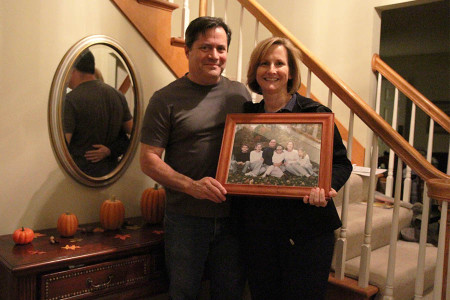 Mr. Victor Trujillo and Mrs. Ann Trujillo stand inside their home holding an old family portrait of their children, Rachel, Erin, Emily and Jacob, Nov. 7.