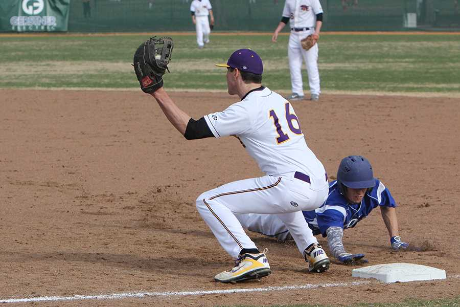Attempting to pick off the runner, Ian Schnurbusch, first base, snags the throw and tries to apply the tag against Northwest, March 31.