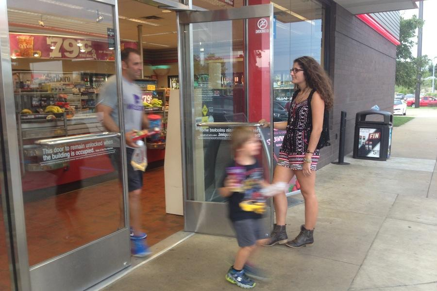 Mary Kay Gagnepain (11) holding the QT door open for Officer Mike and his son.
