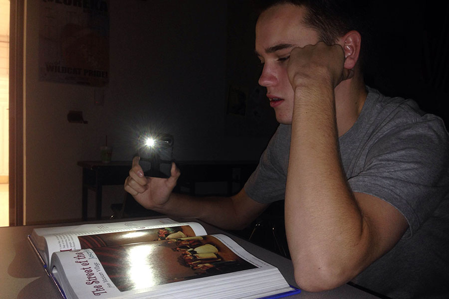 In this photo illustration, Chris Barnett (11) is having major trouble trying to read his textbook without a significant source of light.