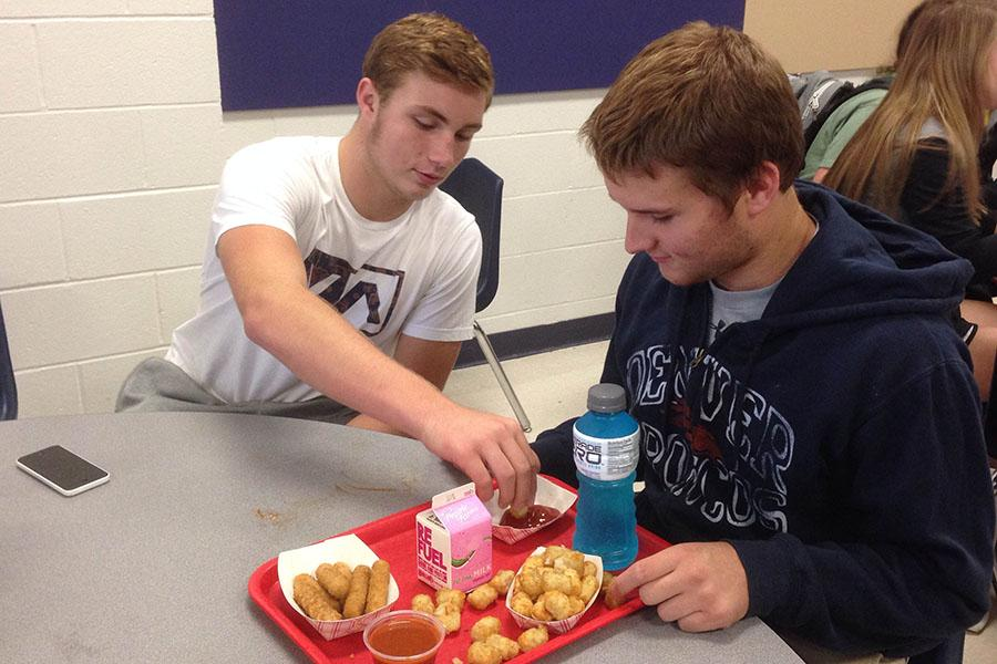 At lunch, Connor McDonald (12) reaches for, Brendan Kloppel's (12)  tator tots.