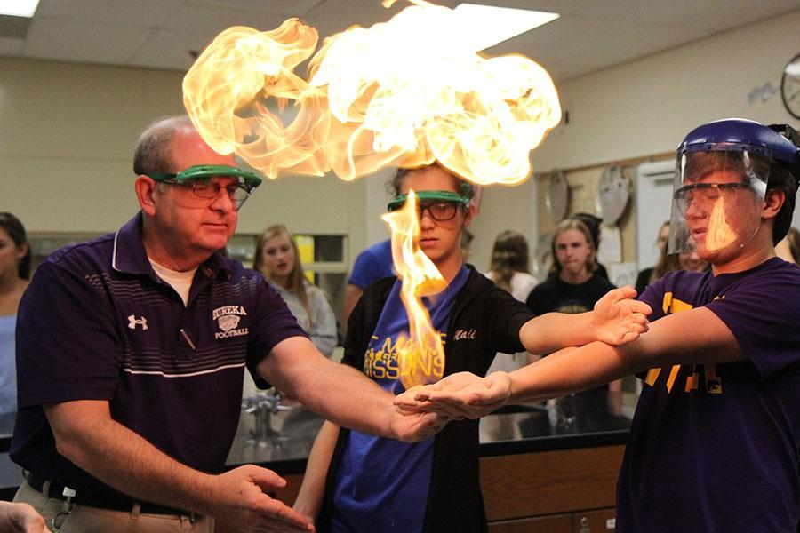 Mole+Day+festivities+heat+up+as+Dr.+Bill+McIlwee%2C+Science+teacher+and+Madeline+Petry%2C+Honors+Chemistry+student%2C+ignite+the+methane+and+soap+bubbles+on+Chemistry+student+Grayson+Henry%27s+hands%2C+Oct.+23.