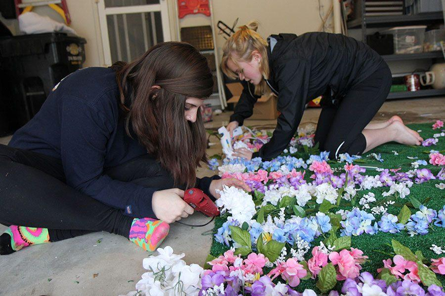 Grace Frauenhoffer, prom committee, and Raegan Waddell, prom committee, create decorations in preparation for prom night, April 7