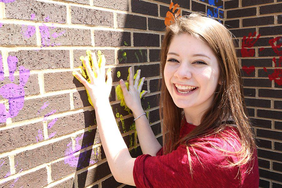 Sarah Wingbermuehle leaves her mark on the wall outside the EHS-hub, May 11.