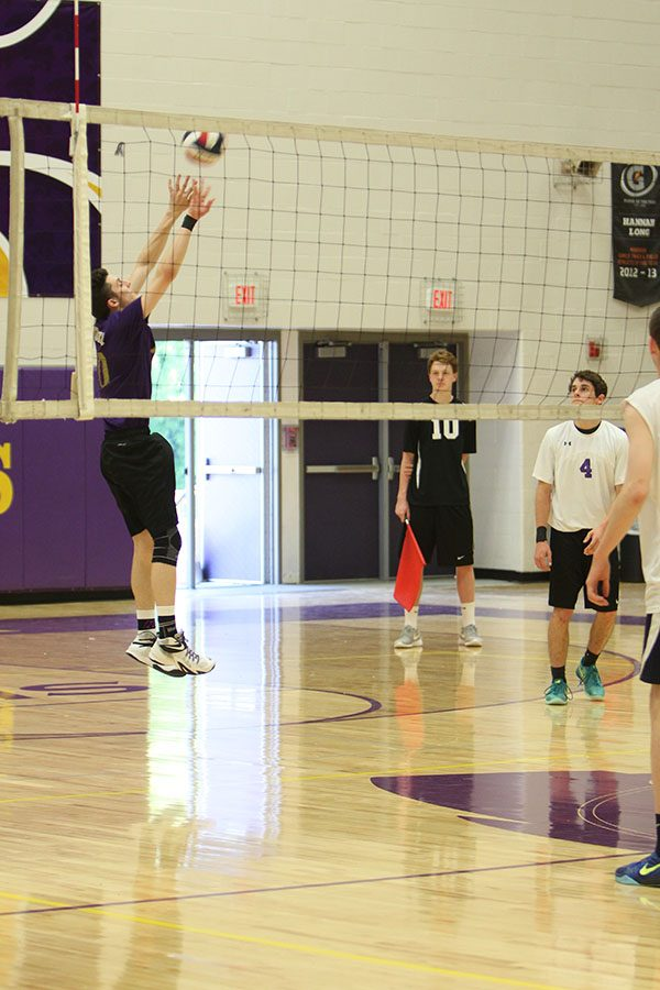 Ethan Mourer (boys varsity volleyball) hits the ball to Marquette High School, May 6.
