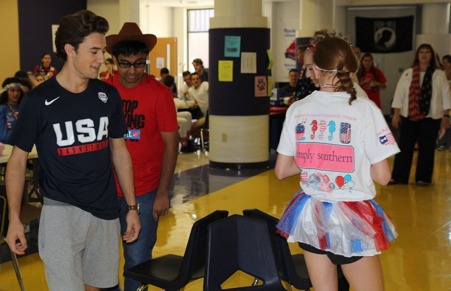 "Seniors take a win after a fierce game of musical chairs as Brendan Pollihan (12) and Rohan Rai (11) compete with other contestants for the remaining chairs during second lunch, Sept. 26. ""I just think it's cool to see everyone participating all week,"" Pollihan said."