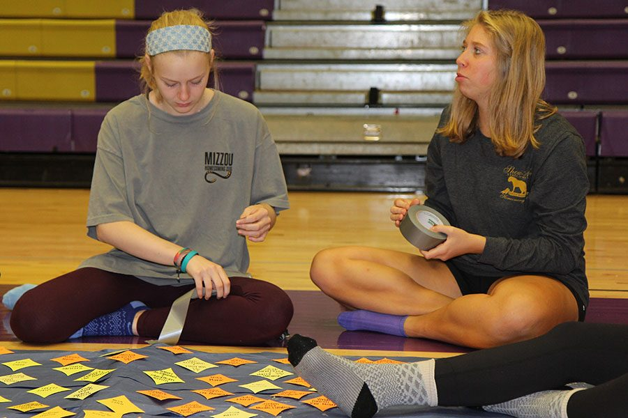 "Names creating a pattern, Kate Griese and Kirstie Ruprecht (12) assemble Homecoming decorations in Gym A, Oct. 1. They taped each attendee's name to the paper that would later line the hallway. ""EHS is one of the only schools who actually hand make their decorations. It's always really elaborate and planned out,"" Ruprecht said. ""It's a really tedious task but it looks amazing once it's finished."""