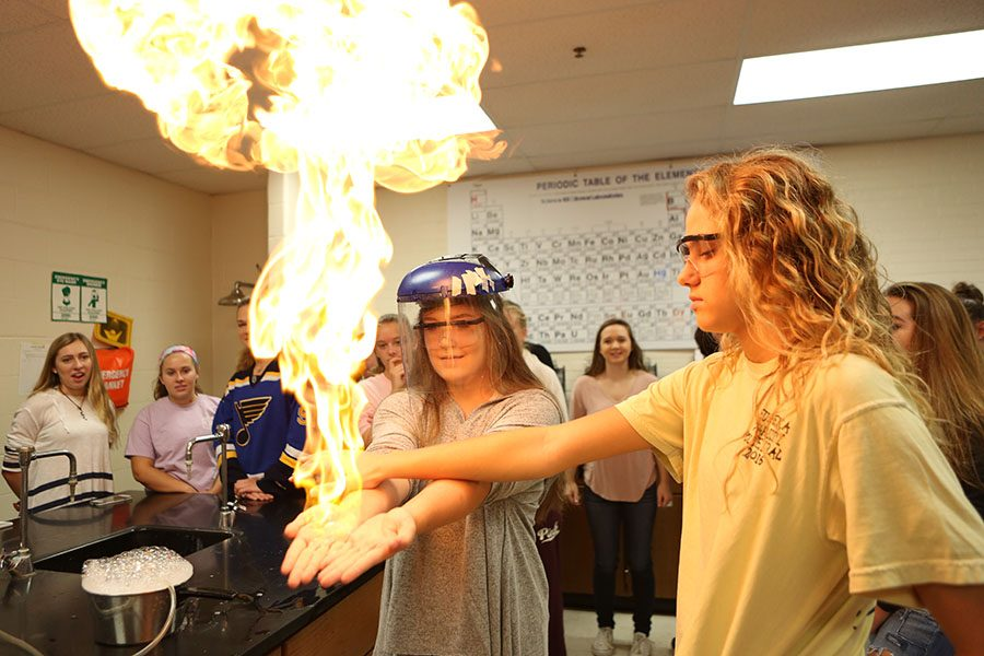 "Mary Jones (11) lights her hands on fire during Mole Day in Mr. Andy Ribbing's first hour class, Oct. 20. ""It was really cool,"" Jones said. ""I did it last year too, though, so it wasn't anything new. I'm in AP Chemistry, so I love it."""
