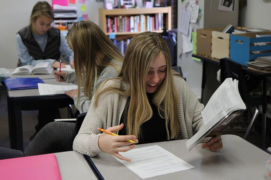 """Finding humor in written word, Isabel Cooper (10) laughs while reading """"Othello"""" in Mrs. Allison Vohsen's seventh hour Honors Language Arts class, Dec. 2. """"The book is pretty funny. I like it so far,"""" Cooper said. """"Shakespeare made inappropriate jokes, so I thought it was funny."""""""