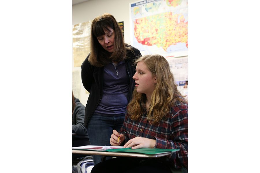 "Getting clarification, Emma Cole (9) asks for help for a DBQ over WWII from Mrs. Kim Eastlund in her seventh hour US History class, Jan. 20. ""I have liked it,"" Cole said. ""I think it's cool to know about what happened in the past."""