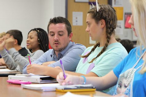 Coach Michael Hanna sits down with Emily Hashbarger (9), Sep. 27, during his sixth hour Algebra 1 class.