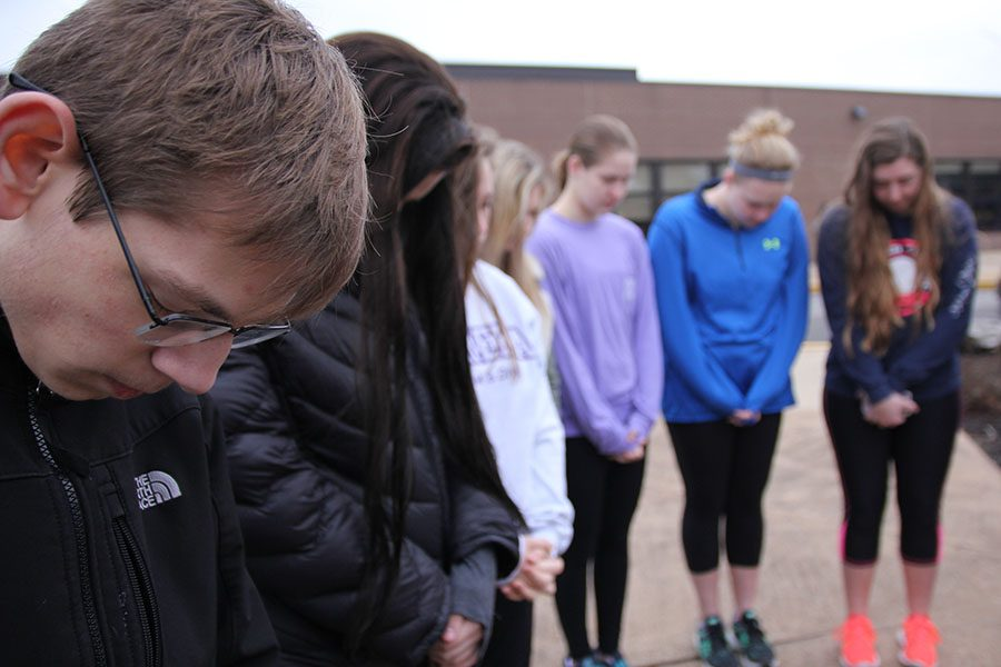 Joe Kruessel (11) prays at the flagpole with members of FCA at their Ash Wednesday service, March 1. Students, teachers and faculty members came out to celebrate the start of the Lent season leading up to the Easter holiday.