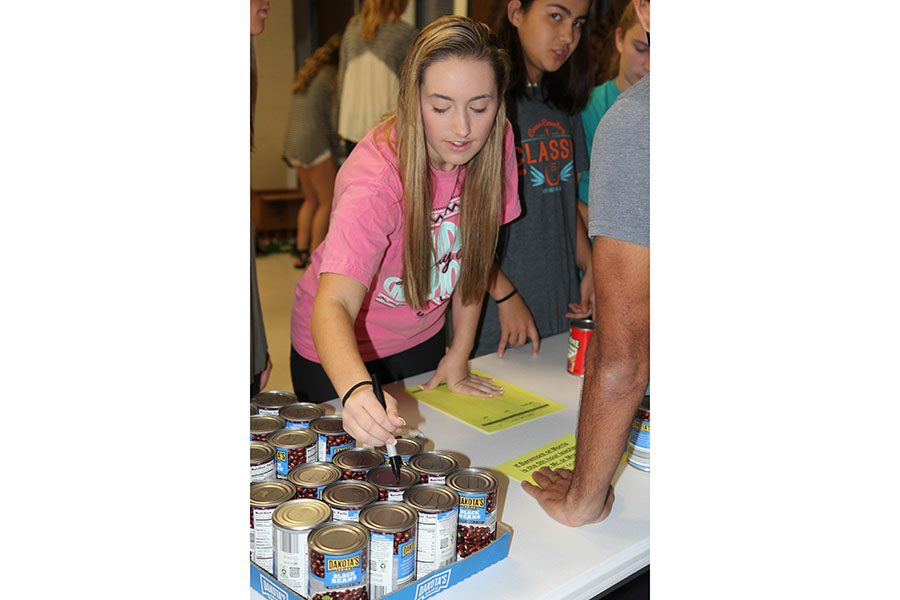 Maddie Ripson (11) helps mark and collect cans for the annual EHS canned food drive, Nov. 3. This is a school-wide project that collects cans for a specific charity of StuCo's choosing.