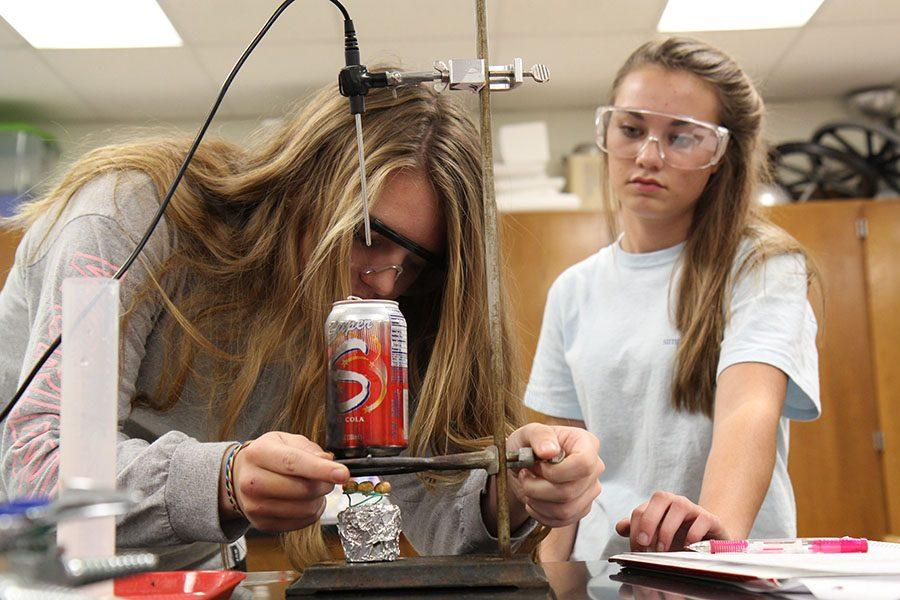 Kirsten Peterson and Madison Woehlke (10) burn peanuts to determine the amount of calories in them for Mike Thebeau's sixth hour Principles of Biomedical class, Nov. 15.
