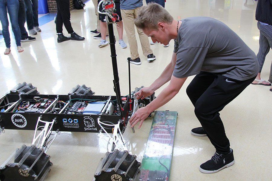 Trevor Fischer (11) interacts with a Mars Rover replica, built by students from Missouri University of Science and Technology, March 27. The S&T students gave Fischer some parts and asked him where he thought the part should go. He experimented.