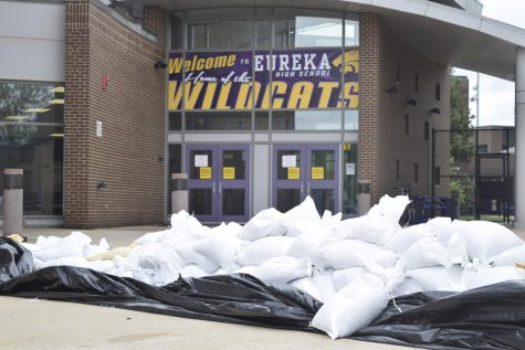 Volunteers prepare for the potential flooding of the school by stacking sandbags, April 30.