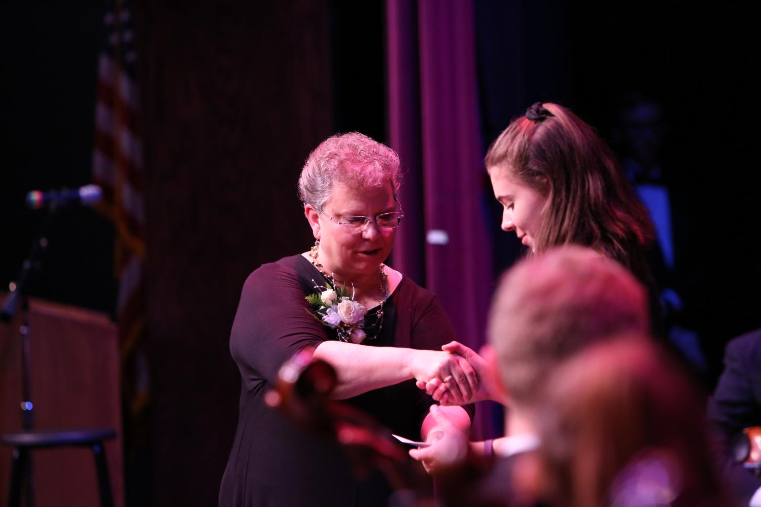 Patti Fleer, orchestra teacher, greets a student at the spring orchestra concert, April 27.