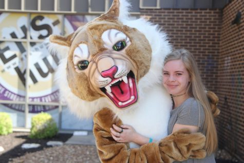 Madison Eble stands in the arms of Wilson the Wildcat as a senior at EHS one last time.