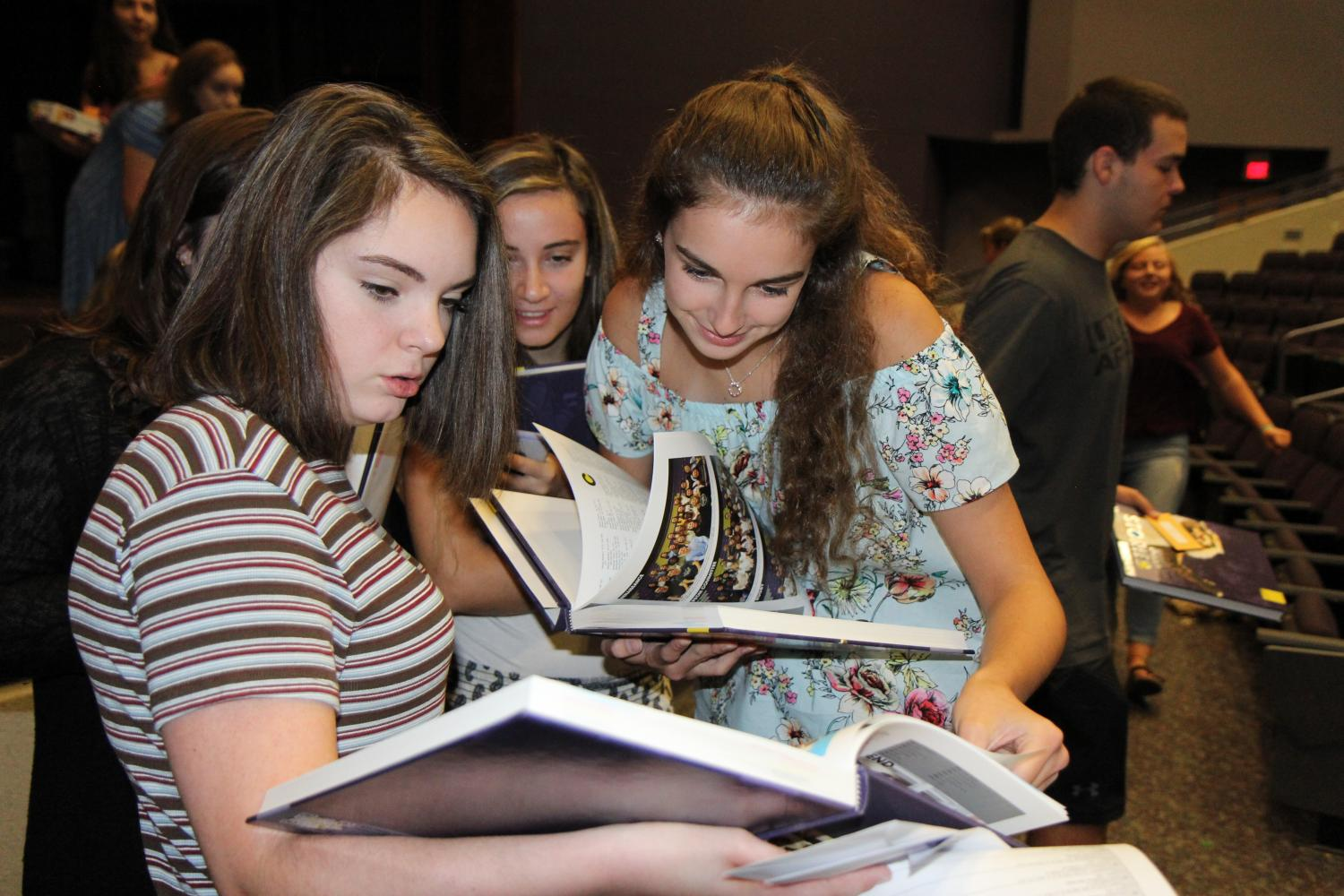 Books finally here, Allyson Dell and Alyce Koch (10) flip through the clubs section attempting to find themselves and friends at orientation, Aug. 9.
