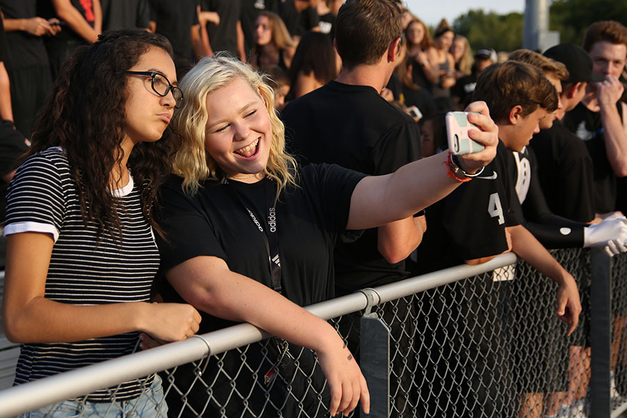 "Catpound filling up, Evellyn Burken (11)  and friend Antonia Melendres, who attends Northwest High School, snap a picture in the stands, Aug. 25. ""It was actually my first time being in the Catpound since I am a new student,"" Burken said. ""It was really fun to be around everyone huddled up. I was a part of a big group and everyone became friends."""