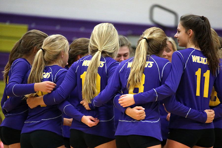 Varsity volleyball huddles together before the game against Oakville, Sept. 19.