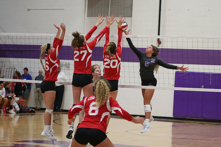 "Emma Lattimore, outside hitter, tips the bal back to Cor Jesu's court, Sept. 5. ""I had three blocks up, and I saw that left back was open so I tried to tip it to score a point,"" Lattimore said. ""At the start, it was really close and we were winning the whole time. Then at the end they won by two points."""