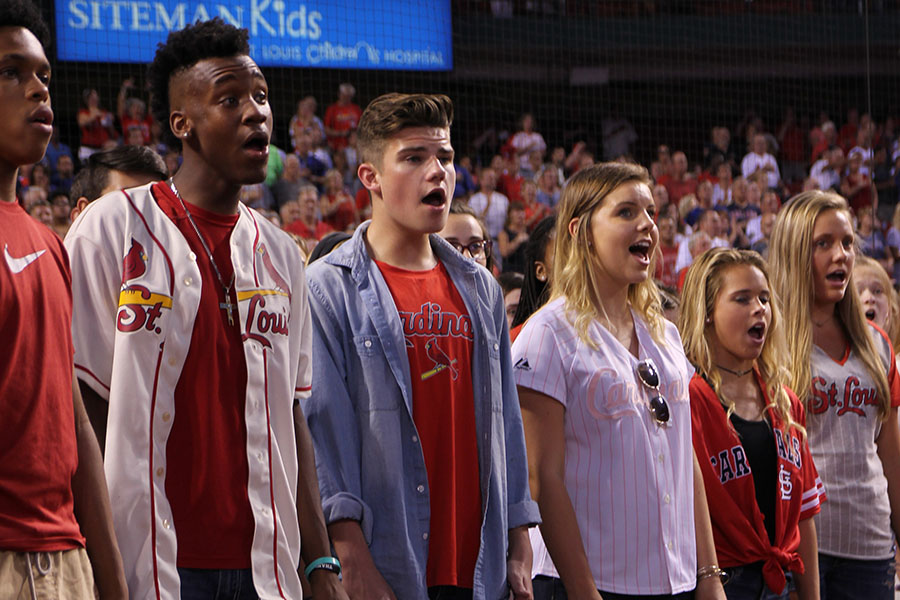 "The first of many lasts, Jerod Turner (12) sings the national anthem at the Cardinals' game for the last time with the choir, Sept. 25. ""What was most fun was getting to perform on the actual field where the Cardinals play,"" Turner said. ""Seeing all the fans who are watching you and your face on the jumbotron it is just exciting. My head was full of thoughts. I was excited, but thinking, 'What are we doing?' I was happy, scared, everything. It is just a rush seeing yourself and your friends up there."""