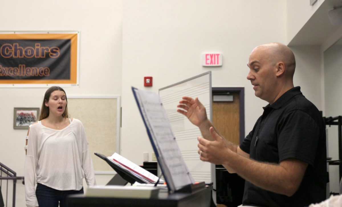 Rebecca Whittaker (12) practice their verses in front of Nathan Schaefferkoetter, choir, during 4th hour Treble Chamber Choir, Sept. 26. Treble Chamber Choir is just one of several choir groups affected by the departure of Charlie Kinnison and the arrival of Nathan Schaefferkoetter.