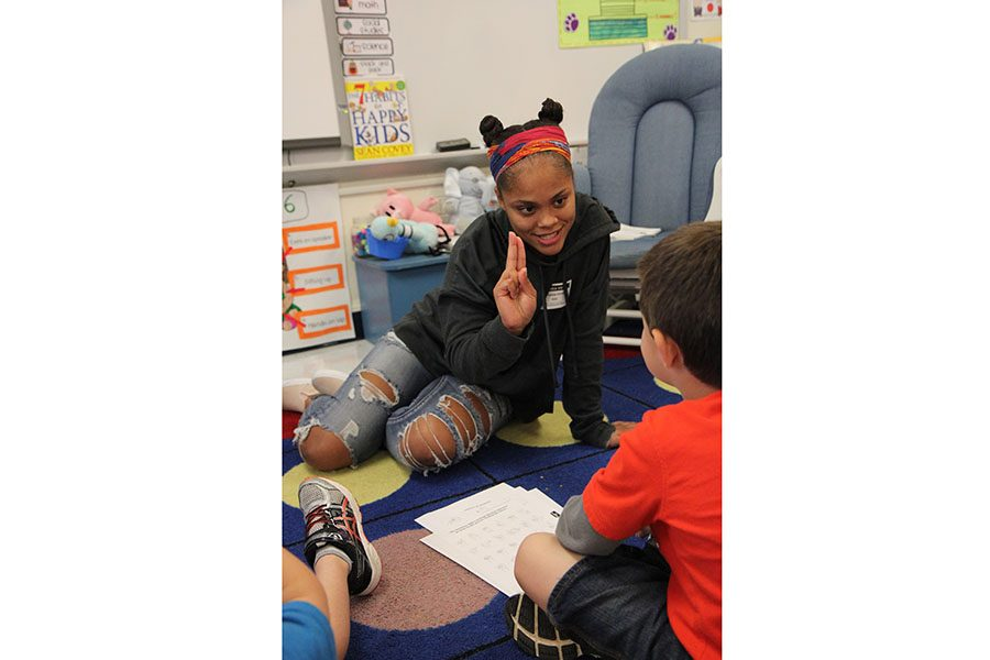 "Connection made, Ariyanna Dixon (11) teaches kindergartners the American Sign Language alphabet and how to spell their name for the ASL 2 field trip to Eureka Elementary School, Oct. 17. ""It was fun to help them learn something new,"" Dixon said. ""We got to see them excited about getting to learn sign language and teach their parents about it when they got home. That isn't something I will forget."""