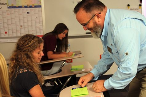 First day of school under way, Rachael Colley talks about the name tag activity with Matt Hillebrand, German, during fourth hour German 1 class, Aug. 16.