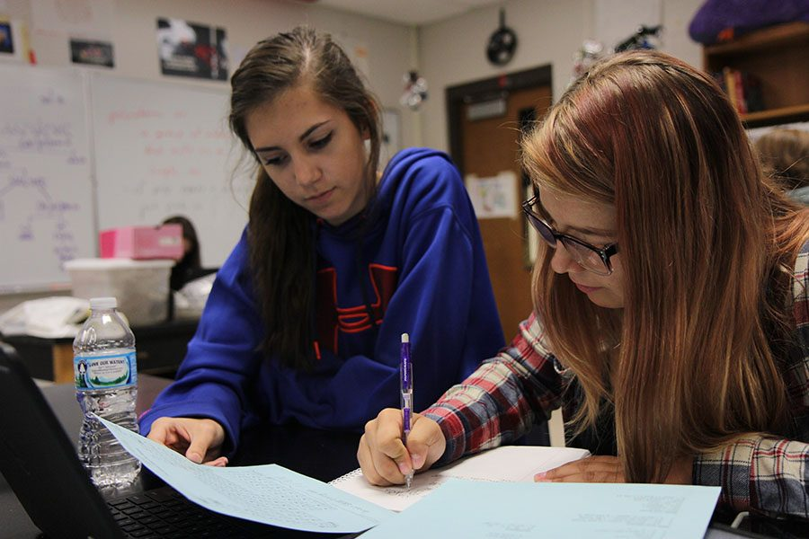 """Compound chemical formulas rewritten, Madeline Petry (12) aids Skylar Maurath (10) during Bill McIlwee's second hour Chemistry class, Sept. 29. """"It was hard for me to write it with carrying everything over, and I knew she would help,"""" Maurath said. """"It is a hard subject to understand, and--since she had already taken the class and is now in Qual--she already knew the information. It is better than asking someone in my class. It's beneficial to have older friends because it kind of grows you up in ways. When they're looking for colleges it helps you to realize you will have to do that, too. It puts everything in perspective."""""""