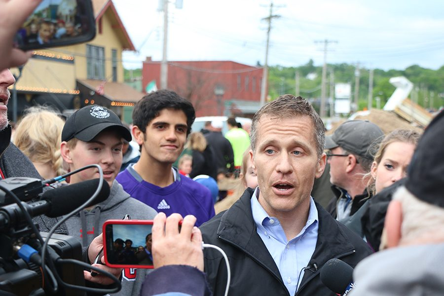 The media and volunteers surrounding them, Nick Cunningham and Alec Holloway (12) listen to Governor Eric Greitens, talk  about the cleanup of the second historic flood in Eureka, May 2.