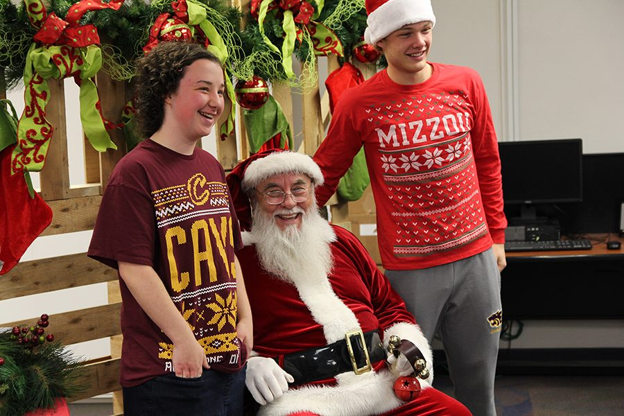 """Spreading the holiday cheer, Lauren Munn (10) and Tyler Kennedy (11) pose with Santa during the Best Buddies Holiday Party, Dec. 10. """"What I like most about Best Buddies is being able to not only put a smile on someone else's faces but also having one on your own,"""" Kennedy said. """"It is the little things like spending time with your buddy or making a gingerbread house with them that make it so enjoyable."""""""