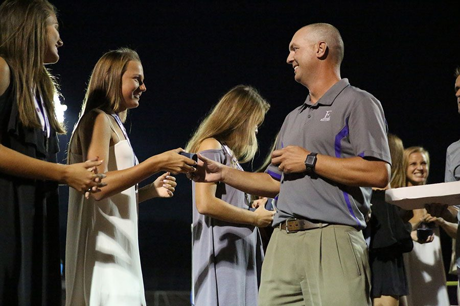 "Reminiscing about their winning season, Hayley Jakovich receives her 2017 soccer state championship ring from head coach, Gary Schneider during halftime at the football game against Francis Howell, Aug. 25. ""I wear my ring every day and it's special to me.  People will look at you when you wear it and say 'Wow, she's a state champ',"" Jackovich said. ""I've been playing since I was five and it's something I love doing. After winning something like that, it makes me want to play even more."" Competing and dominating at the state level as a high school student not only provides long lasting memories of teamwork and dedication, but also gives athletes a drive to continue that success in the sport in the professional league. If St. Louis were to have a professional soccer team, students could go to games more often to learn the sport and maybe one day have a spot on the team."