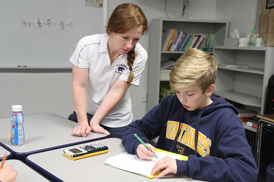"""Functions figured out, Stacey Bevill assists Ethan Mullins (9) with his math homework in second hour Algebra 1, Jan.10. """"I like how small our class is,"""" Mullins said. """"It is easy to get one-on-one help. Our teacher is always helpful. Sometimes I don't understand the problem as fast as the other kids, so I need extra help, and she works with me."""""""