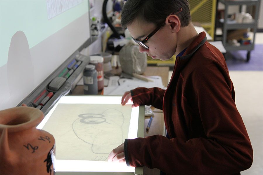 "Light table assisting him, Ryan Skornia (9) sketches Cappy from Super Mario Odyssey for his zentangle in Kristina Welsh's second hour Art Fundamentals class, Jan. 17. ""I like how you can design what you want,"" Skornia said. ""You can free draw and relax. It isn't as stressful as other classes. I like this project because I can implement things that I enjoy like video games. It makes me think about good things, and I don't have to worry about homework or studying. I get to put what is in my mind on paper, and everyone can see it. That makes me happy."""