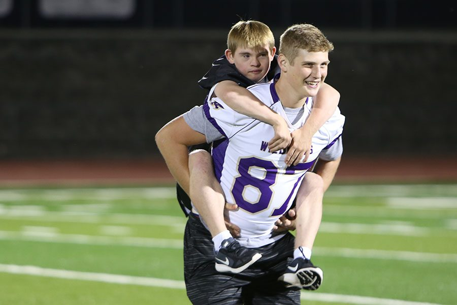 Buddy on board, Thomas Schreiber takes a ride on Avery Taggart's back as they exit the field during the FNL game, Sept. 29.