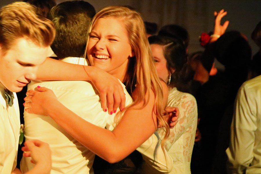 """Lights skimming the crowd, Lauren Glascock hugs Richard Sommers (12) at Winter Formal, Feb.10. """"I liked how casual Winter Formal was,"""" Glascock said. """" It was a lot less stressful to prepare for than some of the other dances. I was happy because we ended up having something to look forward to. I love being able to dress up and have a fun night with my friends. It is pretty upsetting knowing that Winter Formal was one of my last dances. I have made some of the best memories at the dances I have attended over the last four years."""""""