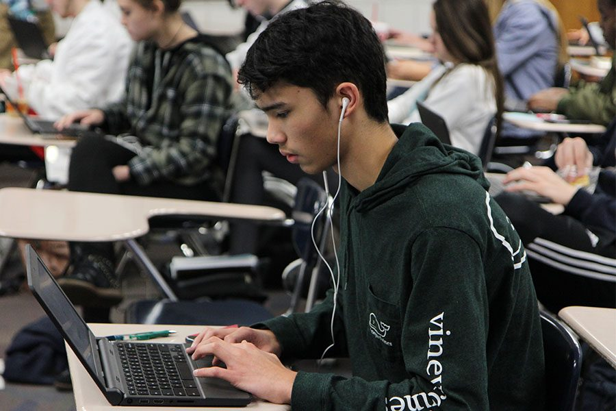 "Nuclear energy his focus, Ethan Munton (11) works on writing his research paper in Todd Trotta's fourth hour LA 11 class, Feb.13. ""At first the research was interesting, but after a while of working, it got boring,"" Munton said. ""I chose nuclear energy because it is interesting and can be a way for future energy power."""