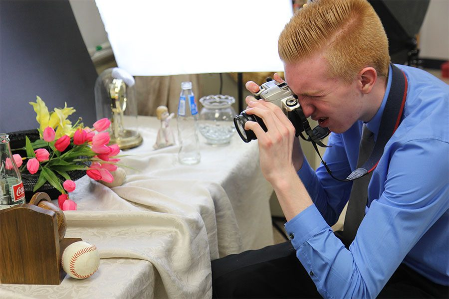 "First time using the camera, Logan Kayser (11) focuses in on a baseball during Robyn Stellhorn's second hour Photo 1 class, Feb.21. ""My thought was no matter what I end up doing for a career, I am going to end up having to take pictures for an event or something, so I might as well learn how to do it right,"" Kayser said. ""I like how using a film camera is a whole process. It is not as easy as taking a picture on a phone. It is more satisfactory because you have to put in a lot more work. Everything has to be right. I enjoy working with cameras because it isn't something I get do all the time."""