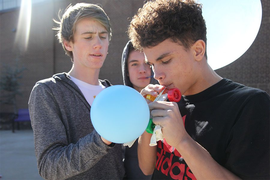 "Attempting to power a car, Casey Baker and Jhalon Asher-Sanders (10) blow up a balloon to use as their fuel in David Klenke's seventh hour Physical Science class, March 2. Physical science was using the balloon air as power to race their toy cars. ""I liked being able to work with all my friends,"" Asher-Sanders said. ""We got to choose our own group instead of having our teacher choose them. It helped me learn how to build something that I didn't know. We didn't have any instructions so we got to be creative and do our own thing."""