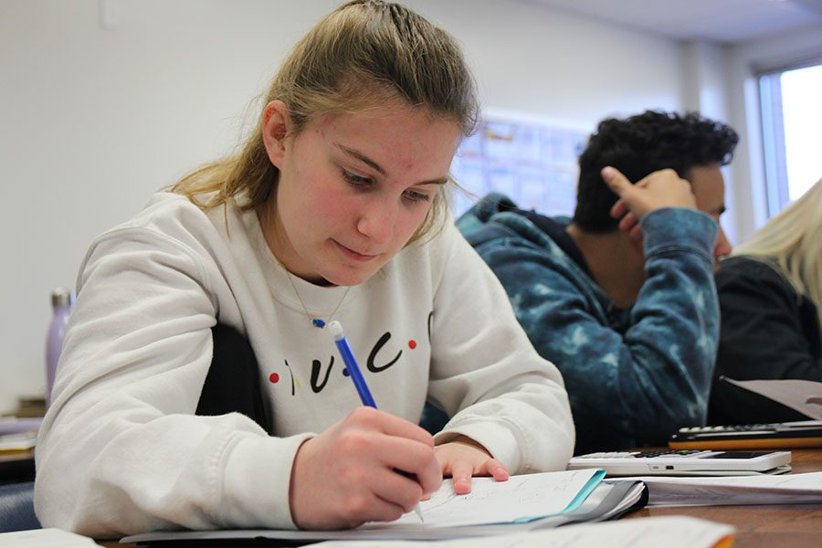 "Midterm packet in front, Megan Mocker (10) works on a problem during Michael McDonald's second hour Algebra 2 class, March 21. ""I was stressed out for the midterm,"" Mocker said. ""A few units were harder than others and some of the concepts were confusing to me. The differences in when to do what steps was hard. The people in my class are nice. I have friends in that class, so we talk and help each other when don't know what we are doing. I studied for it, but I probably could have done better."""