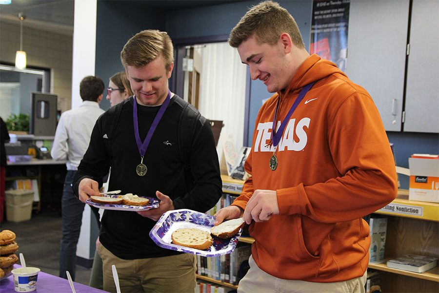 """Ceremony over, William """"Kade"""" Seymour and Benjamin Hunnis grab a bagel after the Stuco Leadership Breakfast, March 6. Coach Jacob Sumner nominated both for their leadership in football.  """"I got an award during our [football] banquet similar to this one,"""" Hunnis said. """"It was for a kid who shows excellence on the field but also in day-to-day life. It felt good to receive them. I didn't purposely try to get them. It just happened. The ceremony just showed how great this school actually is."""""""