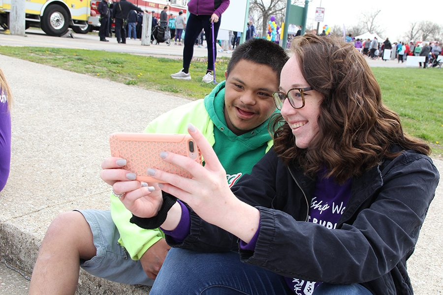 """Walk completed, Colin Smith (10) snaps a selfie with Natalie Olson (12) during the Best Buddies walk for inclusion at Creve Couer Park, April 21. """"The walk was amazing,"""" Olson said. """"I loved being able to hang out with all the buddies and laugh with them. I think it is important to include everyone because everyone deserves to have friends."""""""