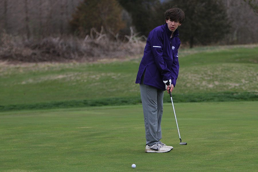 """Wet grass an additional obstacle, William Kvam putts during the match against Parkway South, April 3. """"The sport is relaxing,"""" Kvam said. """"Once we get into the season, the weather is nice, and it is a good way to end the day. It is something that is fun. I didn't play as well as I liked. The ground was wet, and it was cold, so it was a harder game. We are all close on the team and have a lot of fun. We make even the bad games exciting."""" The Wildcats lost 285-261."""