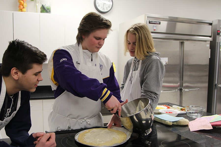"""Fruit pizza in the making, Austin Dust (9) watches as Josh Fowler and Charles Schatz (11) ice the sugar cookie crust during Angela Wilke's second hour Foods 1 class, April 4. """"I like to cook, but I didn't know how, so I wanted to learn,"""" Fowler said. """"I learned a lot about healthy eating. We talk a lot about fruit and vegetables. At home when I am making things, I now include more healthy foods. I like to eat the food over making it. I plan to take Foods 2. The class is fun."""""""